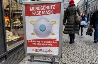 "Shoppers walk past a sign advertising the sale of protective face masks outside a shoe shop in Berlin on February 13, 2020, as the coronavirus ""COVID-19"" epidemic has many people using the masks to prevent the spread of the virus, resulting in stocks running low. (Photo by David GANNON / AFP)"