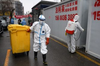 A worker carts a bin loaded with medical waste as another disinfects between containers at the Youan Hospital in Beijing on February 14, 2020. - Youan Hospital is one of twenty hospitals in Beijing treating coronavirus patients. Six health workers have died from the COVID-19 coronavirus in China and more than 1,700 have been infected, health officials said on February 14, underscoring the risks doctors and nurses have taken due to shortages of protective gear. (Photo by GREG BAKER / AFP)