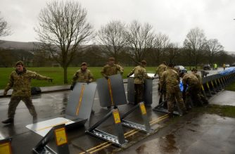 "Members of the 4th Battalion Yorkshire Regiment erect flood barricades in Ilkley, West Yorkshire on February 15, 2020, as Storm Dennis sweeps in over the country. - As Storm Dennis sweeps in, the country is bracing itself for widespread weather disruption for the second weekend in a row. Experts have warned that conditions amount to a ""perfect storm"", with hundreds of homes at risk of flooding. (Photo by Oli SCARFF / AFP)"