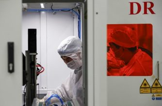This photo taken on February 16, 2020 shows Chinese employees wearing face masks and protective suits working on a smart chip production line in Sihong in China's eastern Jiangsu province. - The death toll from China's new coronavirus epidemic jumped to 1,770 after 105 more people died, the National Health Commission said February 17. (Photo by STR / AFP) / China OUT