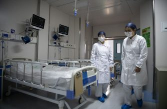 Nurses walk inside a quarantine room at the finished but still unused building A2 of the Shanghai Public Clinical Center, where COVID-19 coronavirus patients will be quarantined, in Shanghai on February 17, 2020. - The death toll from the COVID-19 coronavirus epidemic jumped to 1,770 in China after 105 more people died, the National Health Commission said February 17. (Photo by Noel CELIS / POOL / AFP)