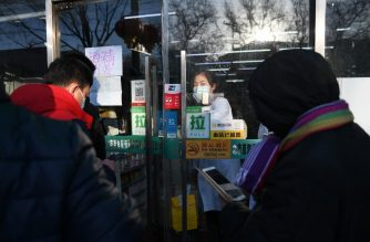 People hoping to buy masks gather outside a pharmacy in Beijing on February 17, 2020. - The death toll from China's COVID-19 coronavirus epidemic jumped to 1,770 after 105 more people died, the National Health Commission said on February 17. More than 70,500 have now been infected nationwide by the virus, which first emerged in December in central Hubei province before spreading across the country. (Photo by GREG BAKER / AFP)