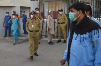 Security personnel (C) and hospital staff wearing facemasks stand outside an hospital entrance in Karachi on February 17, 2020, after a gas leak killed five people and sickened dozens of others in a coastal residential area in Pakistan's port city of Karachi. (Photo by Rizwan TABASSUM / AFP)