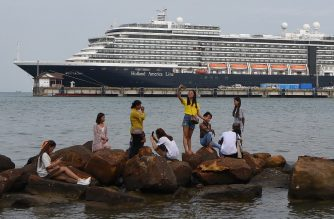 People take pictures on rocks next to the docked Westerdam cruise ship in Sihanoukville on February 18, 2020, as authorities checked if any passengers that remained could have the COVID-19 coronavirus. - A scramble has intensified to trace passengers from a US cruise liner allowed to disembark in Cambodia despite at least one traveller later being diagnosed with the deadly coronavirus. (Photo by TANG CHHIN Sothy / AFP)