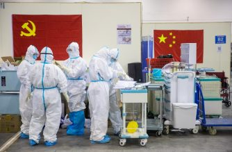 This photo taken on February 17, 2020 shows medical staff members working at an exhibition centre converted into a hospital in Wuhan in China's central Hubei province. - The death toll from the COVID-19 coronavirus epidemic jumped to 1,868 in China on February 18 after 98 more people died, according to the National Health Commission. (Photo by STR / AFP) / China OUT