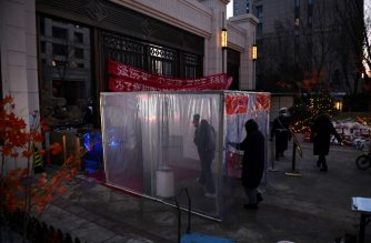 Residents walk through a disinfection channel set up as a protective measure against the COVID-19 coronavirus at the entrance to their compound in Tongzhou, east of Beijing on February 18, 2020. The channel uses humidifiers to spray a mist of disinfectant as residents pass through. - The toll from China's coronavirus epidemic jumped to 1,868 on February 18 after 98 more people died, according to the National Health Commission. (Photo by GREG BAKER / AFP)