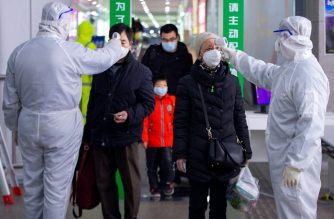 This photo taken on February 18, 2020 shows passengers having their temperature taken as a preventive measure against the COVID-19 coronavirus at a train station in Nanjing, in China's eastern Jiangsu province. - The death toll from China's new coronavirus epidemic jumped past 2,000 on February 19 after 136 more people died, with the number of new cases falling for a second straight day, according to the National Health Commission. (Photo by STR / AFP) / China OUT