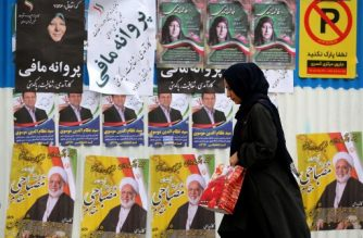(File photo) An Iranian woman walks past electoral posters and fliers during the last day of election campaign in the capital Tehran, on February 19, 2020. - Iran's electoral watchdog today defended its decision to disqualify thousands of candidates for a crucial parliamentary election in two days, as a lacklustre campaign neared its end. Conservatives are expected to make an overwhelming resurgence in Friday's election, which comes after months of steeply escalating tensions between Iran and its decades-old arch foe the United States. (Photo by ATTA KENARE / AFP)