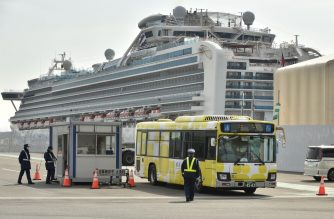 "A bus carrying passengers who disembarked from the Diamond Princess cruise ship (back), in quarantine due to fears of the new COVID-19 coronavirus, leaves the Daikoku Pier Cruise Terminal in Yokohama on February 20, 2020. - Japan hit back at criticism over ""chaotic"" quarantine measures on the coronavirus-riddled Diamond Princess cruise ship, as fears of contagion mount with more passengers dispersing into the wider world. (Photo by Kazuhiro NOGI / AFP)"