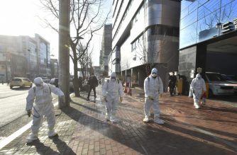 "This handout picture taken on February 19, 2020 by Daegu Metropolitan City Namgu shows South Korean health officials wearing protective suit and spraying disinfectant in front of the Daegu branch of the Shincheonji Church of Jesus in the southeastern city of Daegu as about 40 new cases of the COVID-19 coronavirus confirmed after they attended same church services. - A cluster of novel coronavirus infections centred on a cult church in the South Korean city of Daegu leaped to 39 cases February 20, as the country's total spiked for the second successive day. (Photo by Handout / Daegu Metropolitan City Namgu / AFP) / RESTRICTED TO EDITORIAL USE - MANDATORY CREDIT ""AFP PHOTO / Daegu Metropolitan City Namgu"" - NO MARKETING NO ADVERTISING CAMPAIGNS - DISTRIBUTED AS A SERVICE TO CLIENTS"