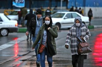 Iranian women wearing protective masks walk in a street in the capital Tehran on February 20,2020. - Two people have died in Iran yesterday after testing positive for the new coronavirus, the health ministry said, in the Islamic republic's first cases of the disease. (Photo by ATTA KENARE / AFP)