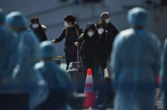 Workers in protective clothes stand by as passengers disembark from the Diamond Princess cruise ship, in quarantine due to fears of new COVID-19 coronavirus, at Daikoku pier cruise terminal in Yokohama on February 21, 2020. - Hundreds of people have been allowed to leave the ship after testing negative for the disease and many have returned to their home countries to face further quarantine. (Photo by Philip FONG / AFP)