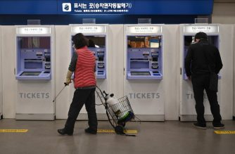 An employee sprays disinfectant at a railway station in the southeastern city of Daegu on February 21, 2020 - South Korea confirmed 52 more cases of novel coronavirus on February 21 as the number of infections linked to a religious sect in Daegu spiked, making it the worst-infected country outside China. (Photo by Jung Yeon-je / AFP)
