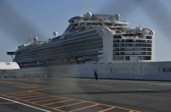 A security guard wearing a facemask, walks next to the Diamond Princess cruise ship, in quarantine due to fears of new COVID-19 coronavirus, at Daikoku pier cruise terminal in Yokohama on February 21, 2020. - Hundreds of people have been allowed to leave the ship after testing negative for the disease and many have returned to their home countries to face further quarantine. (Photo by Philip FONG / AFP)