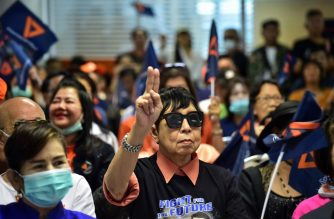 Future Forward Party supporters watch court proceedings at the political party's headquarters in Bangkok on February 21, 2020. - Thailand's Constitutional Court is set to rule on Future Forward Party's dissolution over a loan from its billionaire leader. (Photo by Lillian SUWANRUMPHA / AFP)
