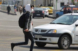 A young Iranian man wearing a protective mask, crosses a busy street in the capital Tehran on February 22, 2020. - Iran today reported one more death among 10 new cases of coronavirus, bringing the total number of deaths in the Islamic republic to five and infections to 28. (Photo by ATTA KENARE / AFP)