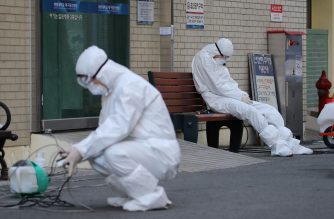 A medical worker wearing protective gear takes a rest as he waits for ambulances carrying patients infected with the COVID-19 coronavirus at an entrance of a hospital in Daegu on February 23, 2020. - South Korea raised its alert on the coronavirus to the highest level on February 23 after reporting three more deaths and 169 new infections. The country has seen a rapid surge in the number of coronavirus cases since a cluster of infections emerged from a religious sect in the southern city of Daegu. (Photo by - / YONHAP / AFP) / - South Korea OUT / REPUBLIC OF KOREA OUT  NO ARCHIVES  RESTRICTED TO SUBSCRIPTION USE