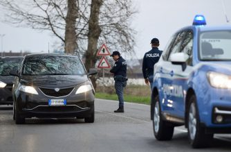 An Italian National Police officer talks to a person in a car at the entrance of the small town of Casalpusterlengo, southeast of Milan, on February 23, 2020, under the shadow of a new coronavirus outbreak, as Italy took drastic containment steps as worldwide fears over the epidemic spiralled. (Photo by Miguel MEDINA / AFP)