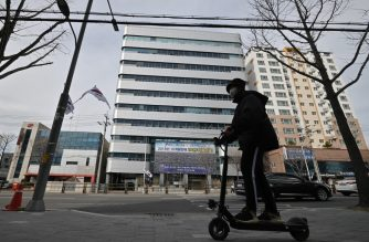A man wearing a face mask rides an electric scooter in front of the Daegu branch of the Shincheonji Church of Jesus in the southeastern city of Daegu on February 24, 2020. - South Korea reported 161 more coronavirus cases on February 24, taking the nationwide total to 763 and making it the world's largest total outside China. The country has seen a rapid surge in the number of coronavirus cases -- adding more than 700 cases in less than a week -- since a cluster of infections emerged from a religious sect in the southern city of Daegu. (Photo by Jung Yeon-je / AFP)