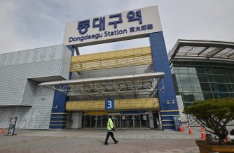 A man wearing a face mask walks in front of Dongdaegu railway station in the southeastern city of Daegu on February 24, 2020. - South Korea reported 161 more coronavirus cases on February 24, taking the nationwide total to 763 and making it the world's largest total outside China. The country has seen a rapid surge in the number of coronavirus cases -- adding more than 700 cases in less than a week -- since a cluster of infections emerged from a religious sect in the southern city of Daegu. (Photo by Jung Yeon-je / AFP)