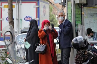 """People wearing protective masks wait along the side of a street in the Iranian capital Tehran on February 24, 2020. - Iran's government vowed on February 24 to be transparent after being accused of covering up the deadliest coronavirus COVID-19 outbreak outside China as it dismissed claims the toll could be as high as 50. The authorities in the Islamic republic have come under mounting public pressure since it took days for them to admit to """"accidentally"""" shooting down a Ukrainian airliner last month, killing 176 people. Iran has been scrambling to contain the outbreak since it announced the first two deaths in the holy city of Qom on February 19. (Photo by ATTA KENARE / AFP)"""