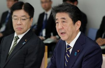 Japan's Prime Minister Shinzo Abe (R) and Health Minister Katsunobu Kato (L) attend a meeting at the new COVID-19 coronavirus infectious disease control headquarters at the prime minister's office in Tokyo on February 26, 2020. - Dozens of passengers who were allowed off a coronavirus-stricken cruise ship have developed symptoms including fever and will be asked to take tests for the virus, Japan's health minister said on February 26. (Photo by STR / JIJI PRESS / AFP) / Japan OUT