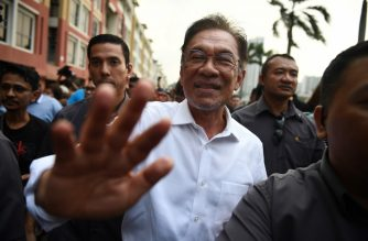 Politician Anwar Ibrahim waves as he leaves after a press conference at the People's Justice Party headquarters in Petaling Jaya, on the outskirts of Kuala Lumpur, on February 26, 2020. - Malaysia's government has collapsed after the resignation of Prime Minister Mahathir Mohamad, which followed a failed bid by rivals to form a new coalition aimed at stopping leader-in-waiting Anwar Ibrahim from succeeding him. (Photo by Mohd RASFAN / AFP)