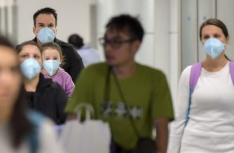 "Passengers, wearing masks as a precautionary measure to avoid contracting the Covid-19 virus, travel through Guarulhos International Airport, in Guarulhos, Sao Paulo, Brazil on February 26, 2020. - The Brazilian Health Ministry confirmed Wednesday the diagnosis of coronavirus of a Brazilian resident in Sao Paulo, which became the first case of this epidemic in Latin America. The initial diagnosis ""was confirmed,"" Minister Luiz Henrique Mandetta said at a press conference in Brasilia. (Photo by NELSON ALMEIDA / AFP)"