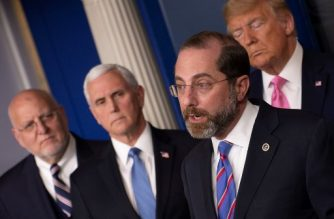 US President Donald Trump (R) and US Vice President Mike Pence (2nd L) listen to US Secretary of Health Alex Azar during a news conference on the COVID-19 outbreak at the White House on February 26, 2020. - US President Donald Trump on Wednesday defended his administration's response to the novel coronavirus, lashing the media for spreading panic as he conducts an evening news conference on the epidemic. (Photo by Eric BARADAT / AFP)