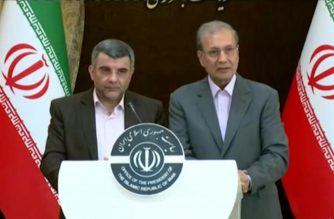 Deputy Health Minister Iraj Harirchi (left) with Ali Rabiei, Iran Government spokesman, during a recent press briefing on the status of the coronavirus disease infections in Iran.  (Screenshot from Iran Press video, as provided by AFPTV)