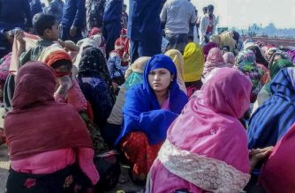 Rohingya refugees wait in an area following a boat capsizing accident, in Teknaf on February 11, 2020. - At least 14 people drowned and dozens more were unaccounted for after a boat carrying Rohingya refugees sank off southern Bangladesh early February 11, officials said. (Photo by STR / AFP)