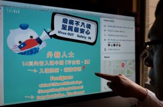 This photo illustration taken on February 14, 2020 shows a man pointing to a webpage from Taiwan's Ministry of Foreign Affairs' Facebook account, used to promote the prevention of the deadly COVID-19 coronavirus, in Taipei. - While China deploys stern communist slogans in its battle against a deadly new coronavirus, democratic Taiwan has embraced cuddly mascots and humour to ease public anxiety and educate on best practices. Images of cute animals have featured in daily social media updates from government agencies to tackle disinformation and prevent infections spreading. (Photo by Sam Yeh / AFP) / TO GO WITH Taiwan-China-politics-health,FOCUS by Amber WANG