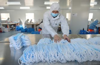 This photo taken on February 18, 2020 shows a worker sorting face masks being produced to satisfy increased demand during China's COVID-19 coronavirus outbreak, at a factory in Nanjing, in China's Jiangsu province. - The medical equipment factory switched surgical instruments and dental equipment production lines to a mask production line to meet the increased demand. (Photo by STR / AFP) / China OUT
