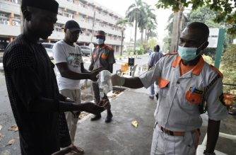 A securityman administers sanitiser to a visitor to a state hospital in Lagos, on February 28, 2020. - Residents of Nigeria's economic hub Lagos scrambled for hygiene products after the chaotic megacity of 20 million announced the first confirmed case of new coronavirus in sub-Saharan Africa. Health Minister Osagie Ehanire said in a statement overnight that the infected person was an Italian citizen who flew in from Milan, at the heart of Europe's largest outbreak, earlier this week. (Photo by PIUS UTOMI EKPEI / AFP)