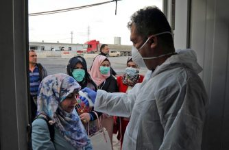 A medic checks the body temperature of travelers arriving to the checkpoint of Arbil, the capital of the northern Iraqi Kurdish autonomous region, on March 2, 2020, as a measure to prevent a novel coronavirus outbreak. (Photo by SAFIN HAMED / AFP)