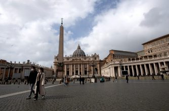 Tourists wearing a protective mask walk in St. Peter's square at the Vatican on March 03, 2020. - Italy urged tourists spooked by the coronavirus not to stay away, but efforts to reassure the world it was managing the outbreak were overshadowed by confusion over case numbers. Hotel bookings in Milan have plummeted to 20 percent, compared to nearly 90 percent normally at this time of year, while in Rome, far from the northern hotspots over 50 percent of bookings have been cancelled until the end of March, hotel association Federalberghi said. (Photo by Tiziana FABI / AFP)