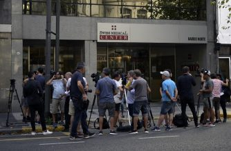 Journalists gather outside the private health center where the first Argentine infected with the new Coronavirus, COVID-19, is located, in Buenos Aires, on March 3, 2020. - Argentinian Health Minister Ginés González García confirmed on Tuesday, March 3, 2020, the first case of Coronavirus in the country on a patient who returned from a trip to Italy and is now isolated on a health center. (Photo by JUAN MABROMATA / AFP)
