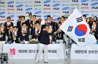 (FILES) In this file photo taken on August 14, 2012 Lee Kee-Heung (C), head of the South Korean athletic delegation for the London Olympics, waves the national flag during a disbandment ceremony as they arrive at Incheon airport, west of Seoul. - The travel restrictions being imposed around the world on arrivals from South Korea are plunging its athletes' Olympic preparations into turmoil, with some considering self-imposed exile to avoid disruptions in the run-up to Tokyo. (Photo by Jung Yeon-je / AFP)