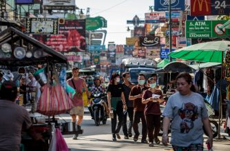 People wear facemasks amid concerns over the spread of the COVID-19 novel coronavirus while walking along Khao San Road, a popular area for tourists in Bangkok on March 6, 2020. (Photo by Jack Taylor / AFP)