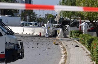 Forensic experts investigate at the scene of an explosion near the US embassy in the Tunisian capital Tunis on March 6, 2020. - A blast that rocked Tunis today was an attack that targeted the US embassy and caused injuries among policemen, police said. A police official said an assailant had tried to enter the embassy but was prevented by police who guarded the diplomatic mission in the Berges du Lac district. (Photo by Fethi Belaid / AFP)