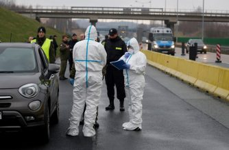 A picture taken on March 9, 2020 on the Polish side shows Polish police, border guards and medical staff, with protective clothing, proceeding to sanitary checks on drivers at Jedrzychowice border crossing, between Poland and Germany, in a measure to protect against the spread of the novel coronavirus. - The introduction of the controls, which are to be rapidly extended to all of Poland's borders, was announced to the media by Polish Prime Minister and consist on measuring people's temperature and filling documents. (Photo by Odd ANDERSEN / AFP)