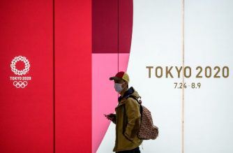 A man wearing a face mask walks in the tunnel of a metro station with the board of the official 2020 Summer Olympics advertisment in Tokyo on March 11, 2020. - Japan and Olympic organisers are at pains to insist this summer's Games in Tokyo are on, despite the new coronavirus outbreak. (Photo by Philip FONG / AFP)