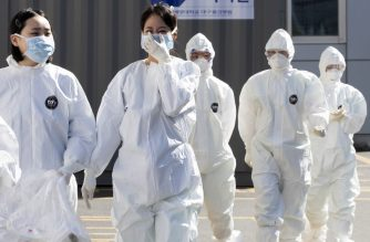 Medical staff members wearing protective gear arrive for their shift to care for patients infected with the COVID-19 coronavirus, at a hospital in Daegu on March 11, 2020. - South Korea announced its first rise in new coronavirus cases for five days on March 11, following a run of declines that have raised hopes the outbreak is coming under control. A total of 242 infections were confirmed on March 10 taking the South's total to 7,755. (Photo by - / YONHAP / AFP) / - South Korea OUT / REPUBLIC OF KOREA OUT  NO ARCHIVES  RESTRICTED TO SUBSCRIPTION USE