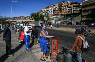 """A woman waiting to buy a propane gas canister wears a face mask as a preventive measure against the spread of the new coronavirus, COVID-19, in Caracas, on March 17, 2020. - People in crisis-weary Caracas woke up Monday to a """"collective quarantine"""" after President Nicolas Maduro ordered the Venezuelan capital's six million population to stay at home to curb the spread of the coronavirus. (Photo by Cristian HERNANDEZ / AFP)"""