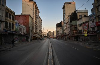 """A man walks along an empty street at Karakoy as the nation tries to limit the spread of the new coronavirus, COVID-19, in Istanbul on March 17,2020. - Turkey suspended collective mosque prayers until further notice to limit the spread of the new coronavirus, while ordering the closure of public spaces including cinemas. The interior ministry said theatres, cinemas, concert halls, restaurants where there is live music, shisha cafes and places serving tea and coffee, night clubs, bars would be closed """"temporarily"""" from midnight  on March 16, 2020. (Photo by Ozan KOSE / AFP)"""