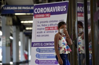 A girl uses a face mask as a precautionary measure against the spread of the new coronavirus, COVID-19, at Bogota's bus terminal on March 17, 2020. (Photo by Raul ARBOLEDA / AFP)
