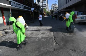 City workers wearing protective suits disinfect a street, as a preventive measure against the COVID-19 coronavirus, in Manila on March 19, 2020. (Photo by Ted ALJIBE / AFP)