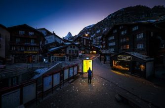 This photograph taken on March 18, 2020, shows a pedestrian looking at an illuminated map board in the empty streets of the Alpine resort of Zermatt, with the Matterhorn mountain amid the spread of the COVID-19 caused by the novel coronavirus. - The Swiss government on March 16, 2020 declared a state of emergency lasting until April 19 in a bid to combat the coronavirus pandemic. All shops, restaurants, bars, entertainment and leisure facilities had to shut down, with the exception of grocery stores, pharmacies and health facilities. (Photo by VALENTIN FLAURAUD / AFP)