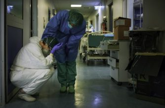 "A nurse wearing protective mask and gear comforts another as they change shifts on March 13, 2020 at the Cremona hospital, southeast of Milan, Lombardy, during the country's lockdown aimed at stopping the spread of the COVID-19 (new coronavirus) pandemic. - After weeks of struggle, they're being hailed as heroes. But the Italian healthcare workers are exhausted from their war against the new coronavirus. (Photo by Paolo MIRANDA / AFP) / RESTRICTED TO EDITORIAL USE - MANDATORY CREDIT ""AFP PHOTO / PAOLO MIRANDA"" - NO MARKETING - NO ADVERTISING CAMPAIGNS - DISTRIBUTED AS A SERVICE TO CLIENTS"