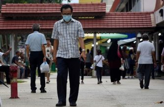 A man, wearing a face mask as a preventive measure against the COVID-19 novel coronavirus, walks around his neighbourhood in Singapore on March 21, 2020. (Photo by Catherine LAI / AFP)